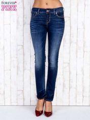 Ciemnoniebieskie jeansowe spodnie slim z przetarciami