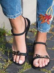 Czarne sandały z ozdobną czarną kokardką i złotą blaszką na przodzie zapinane na sprzączkę