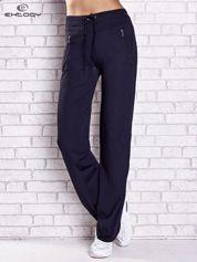 Granatowe spodnie dresowe z kieszeniami i przeszyciami