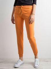 Jasnopomarańczowe spodnie dresowe z troczkami