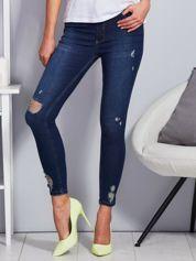 Niebieskie jeansy z przedarciami na nogawkach