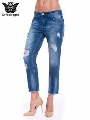 Niebieskie spodnie girlfriend jeans z poszarpaną na dole nogawką
