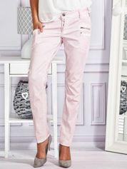 Różowe materiałowe spodnie skinny z dekatyzacją i suwakami