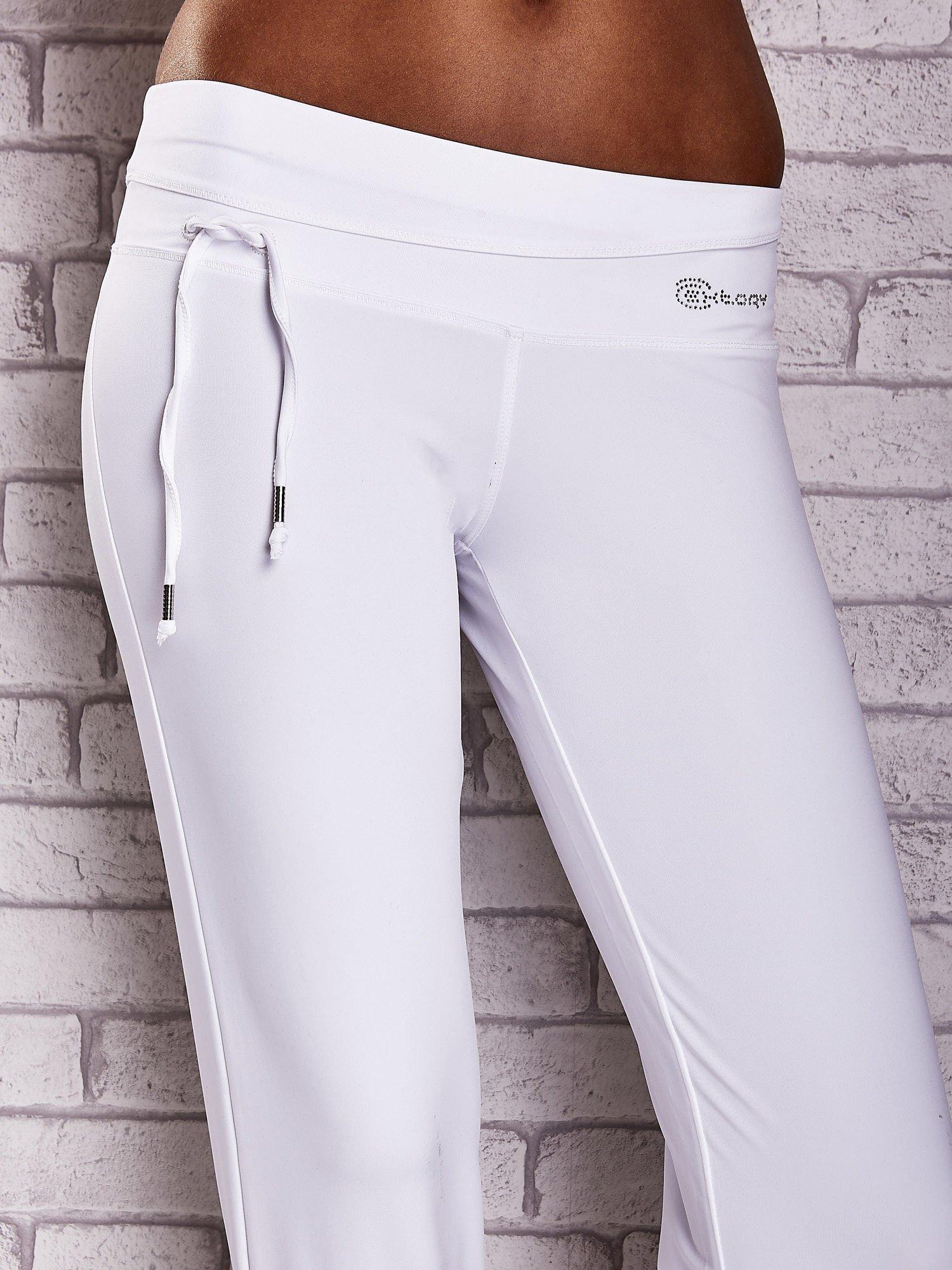 Białe śliskie spodnie capri z dżetami i troczkami                                  zdj.                                  4