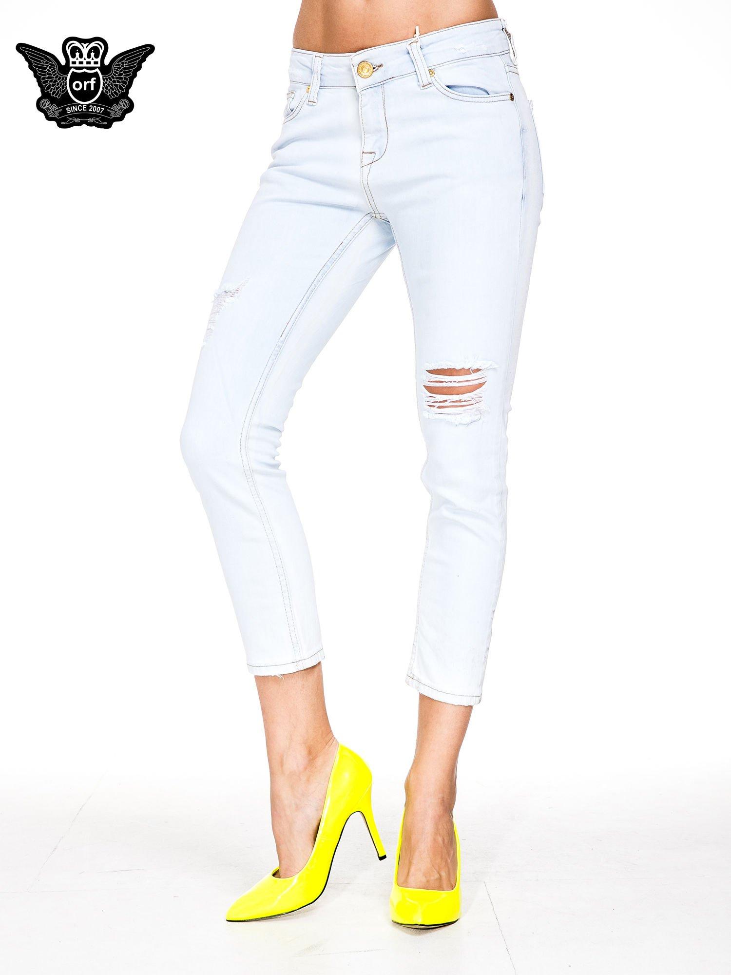 Błękitne spodnie skinny jeans z rozdarciem na udzie                                  zdj.                                  1