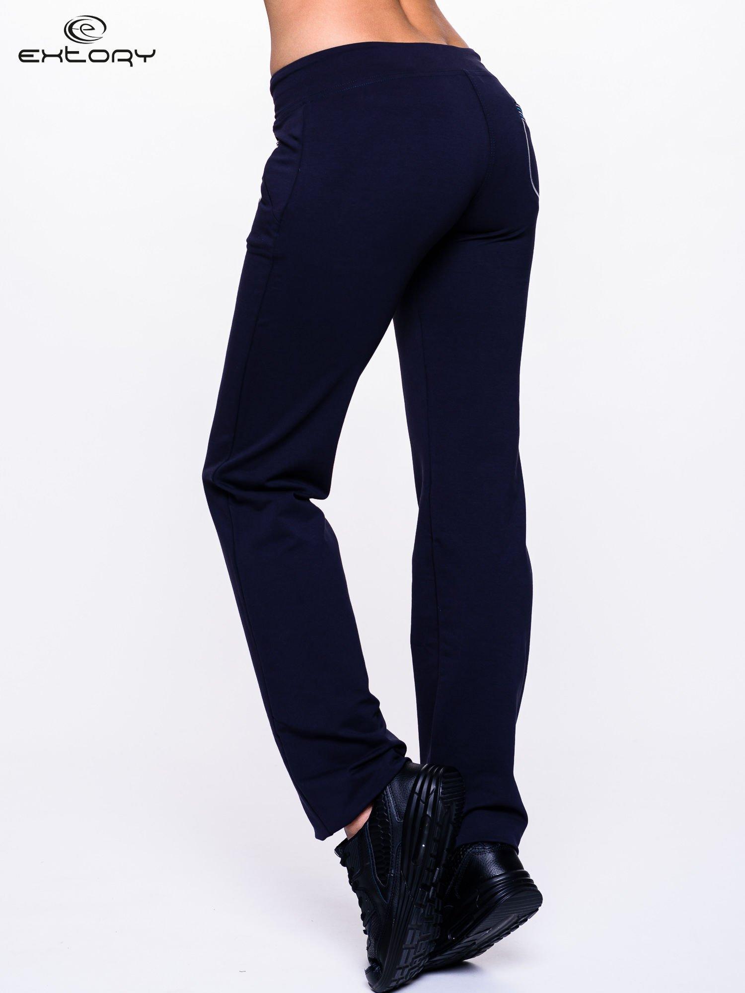 Ciemnogranatowe spodnie dresowe z turkusową wstawką                                  zdj.                                  4