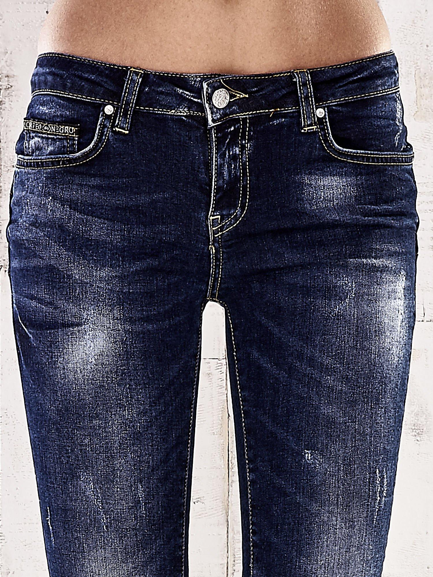 Ciemnoniebieskie spodnie rurki z dekatyzowaniem i przetarciami                                  zdj.                                  4