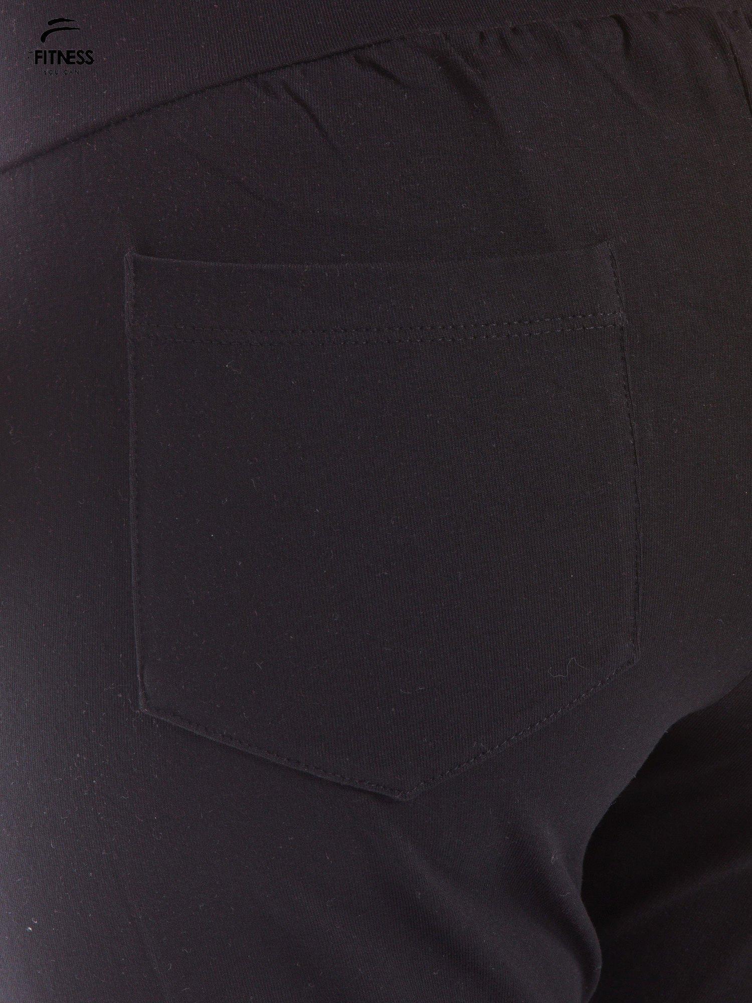 Czarne dresowe spodnie damskie ze ściągaczem i błyszczącym sznurkiem                                  zdj.                                  4