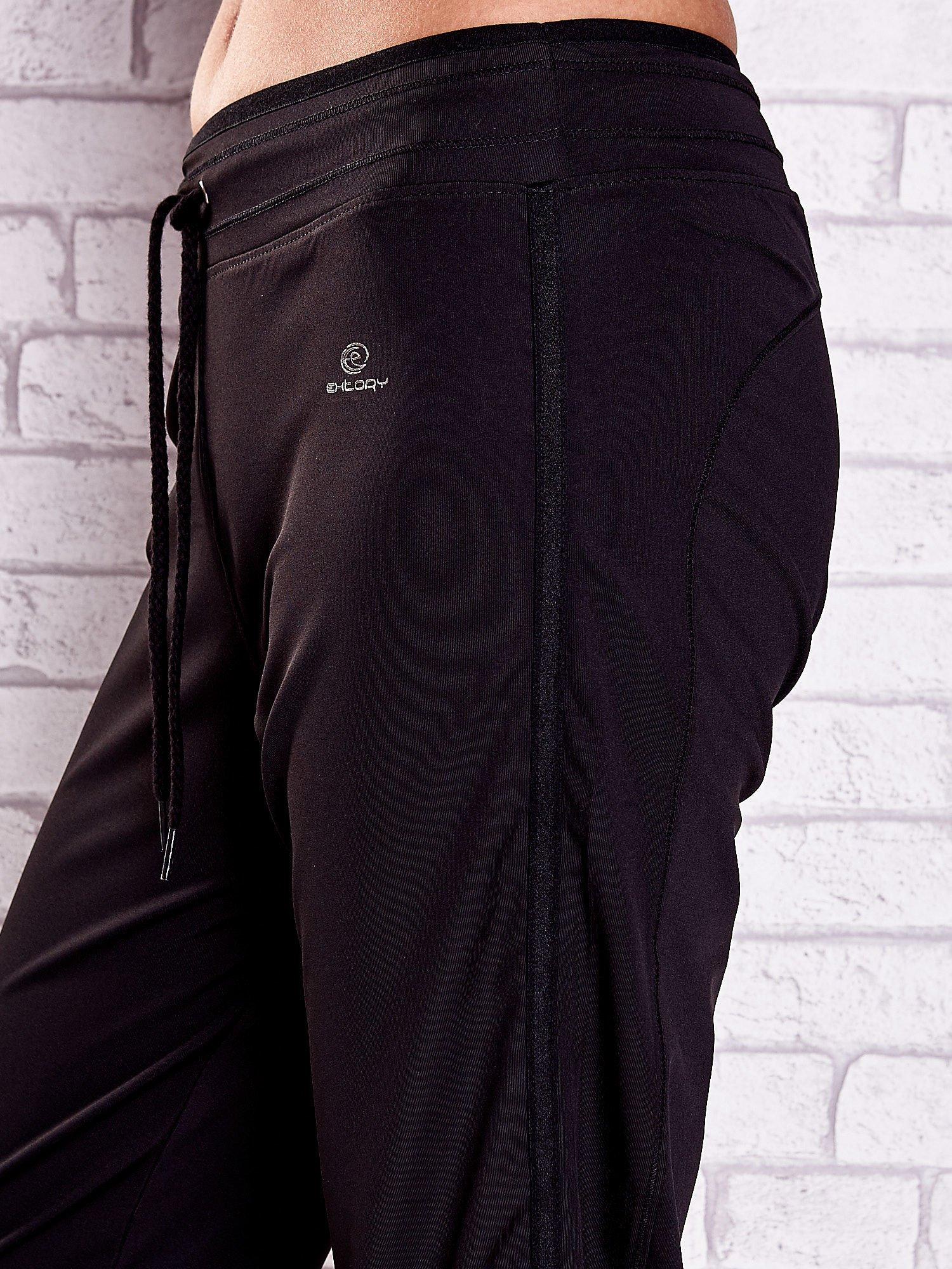 Czarne spodnie capri z lampasami i troczkami PLUS SIZE                                  zdj.                                  5