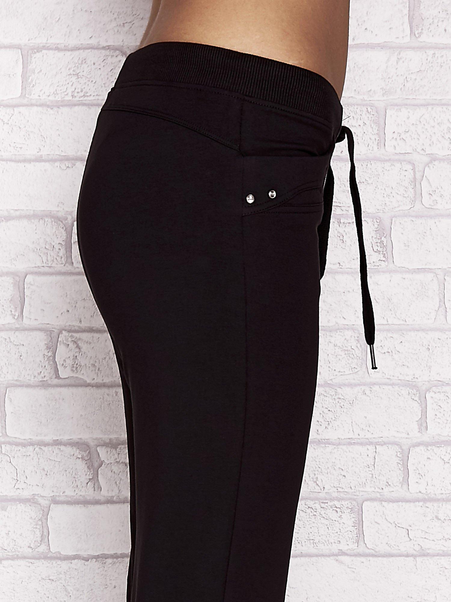 Czarne spodnie dresowe capri z aplikacją na kieszeniach                                  zdj.                                  5