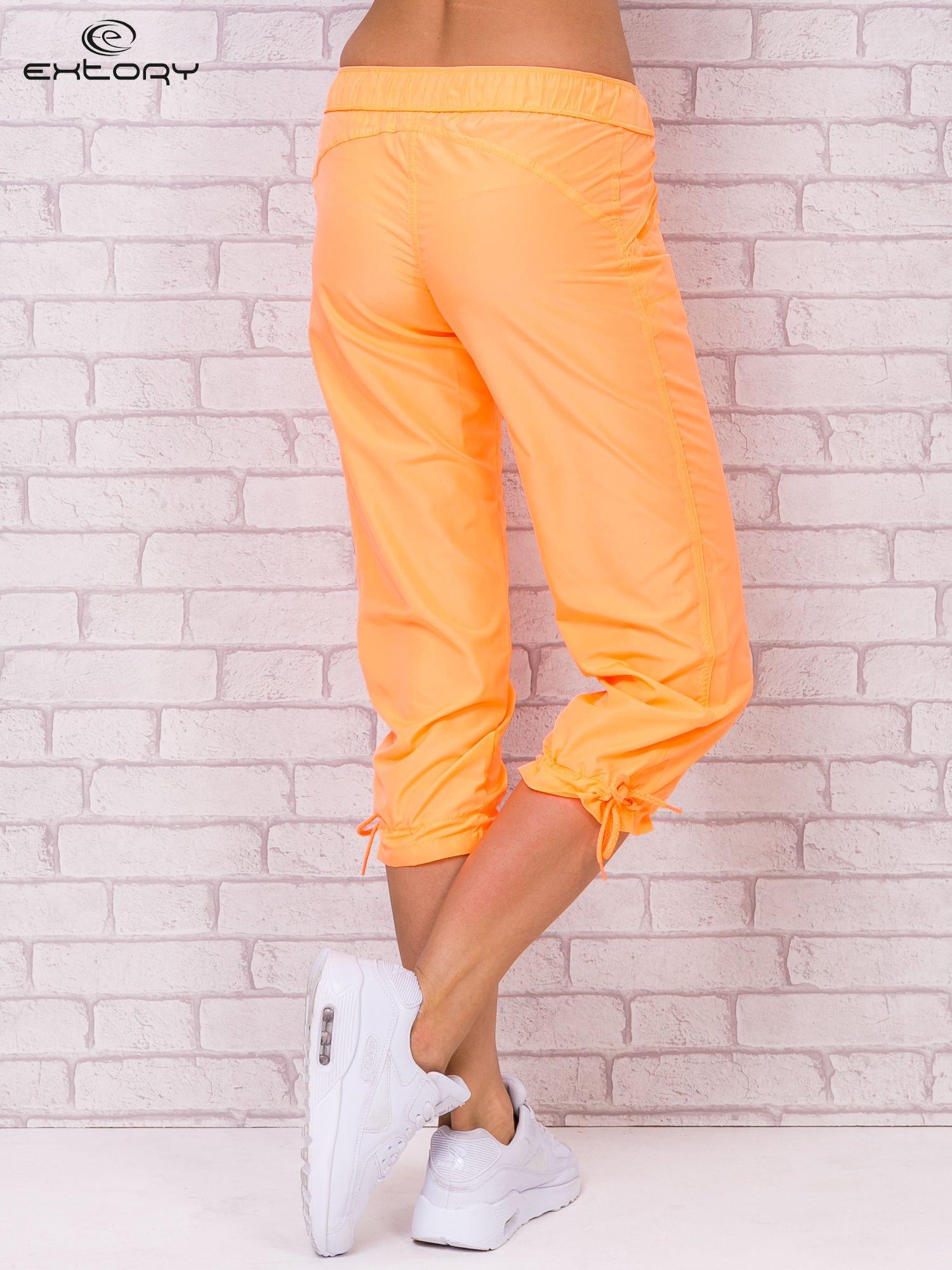 Fluopomarańczowe spodnie sportowe capri z wiązaniem                                  zdj.                                  2
