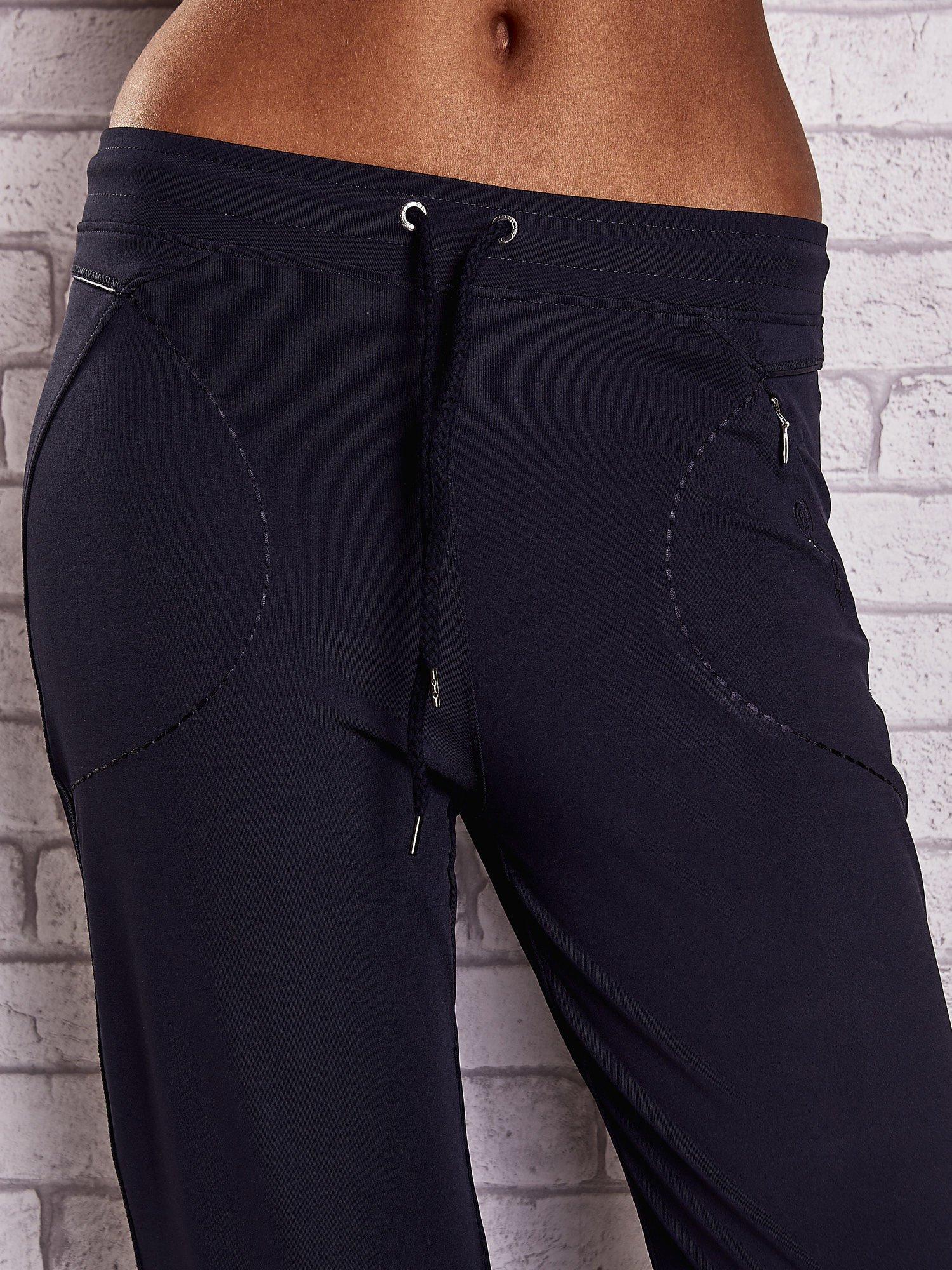 Granatowe spodnie capri z kieszonką i haftem PLUS SIZE                                  zdj.                                  4