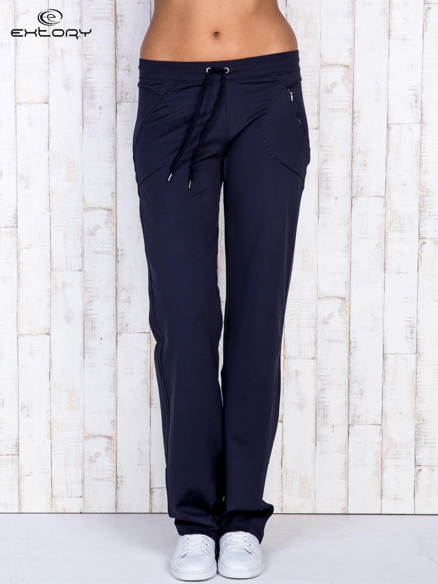Granatowe spodnie dresowe z kieszonką i haftem PLUS SIZE                                  zdj.                                  1