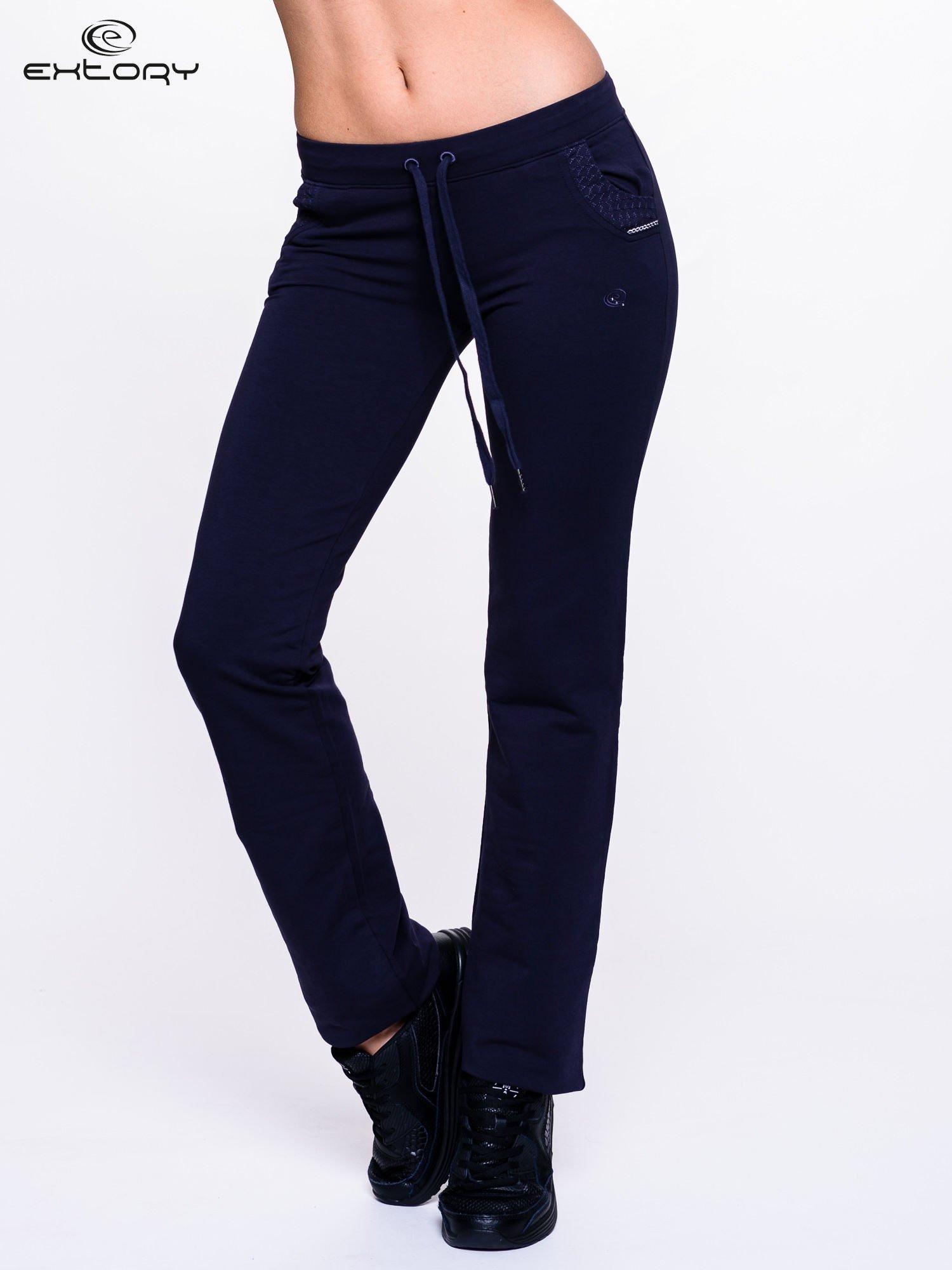Granatowe spodnie dresowe ze wzorzystą wstawką przy kieszeniach                                  zdj.                                  1