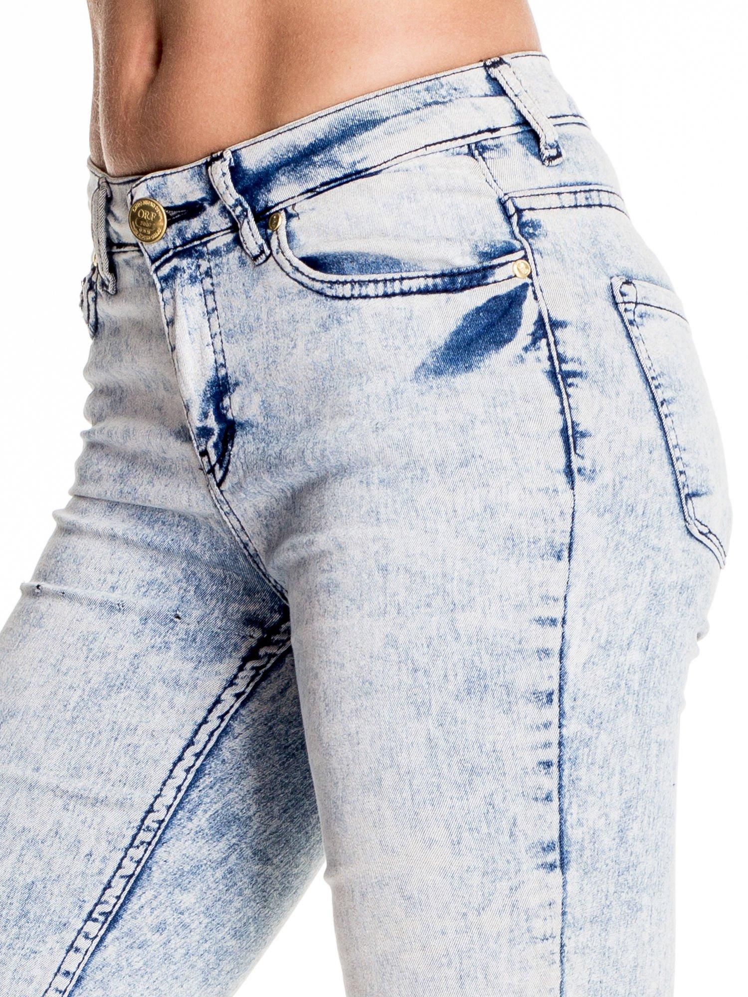 Jasnoniebieskie marmurkowe spodnie skinny jeans z rozdarciami na kolanach                                  zdj.                                  5