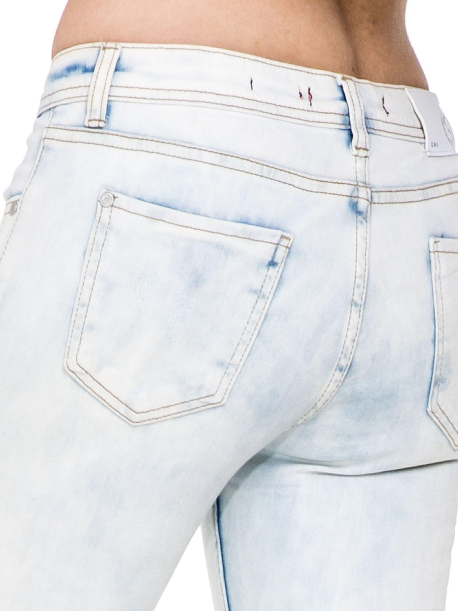 Jasnoniebieskie rozjaśniane spodnie jeaansowe rurki z rozdarciami na kolanach                                  zdj.                                  6