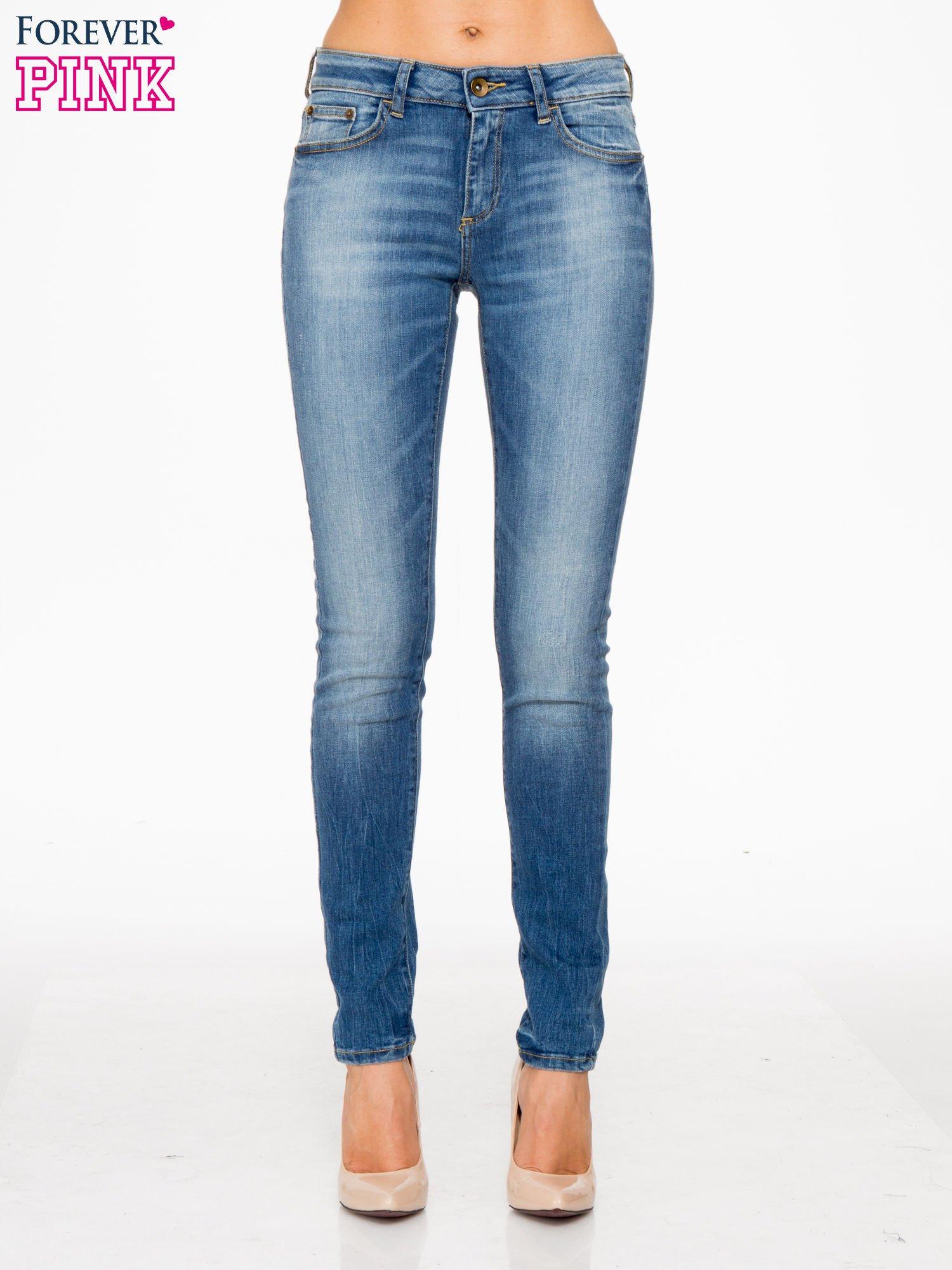 Jasnoniebieskie spodnie jeansowe rurki z przeszyciami na kieszeniach                                  zdj.                                  1