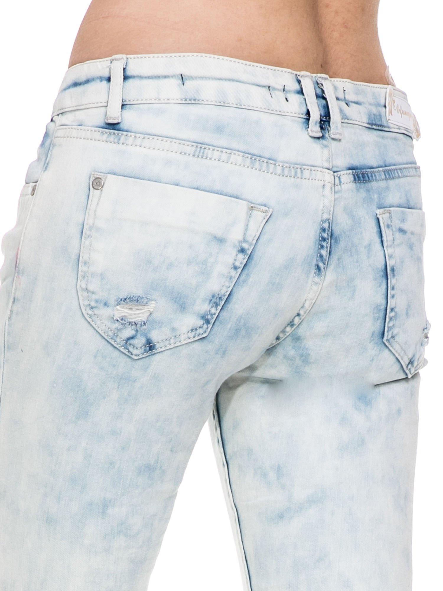 Jasnoniebieskie spodnie jeansowe rurki z przetarciami i poszarpaną na dole nogawką                                  zdj.                                  7