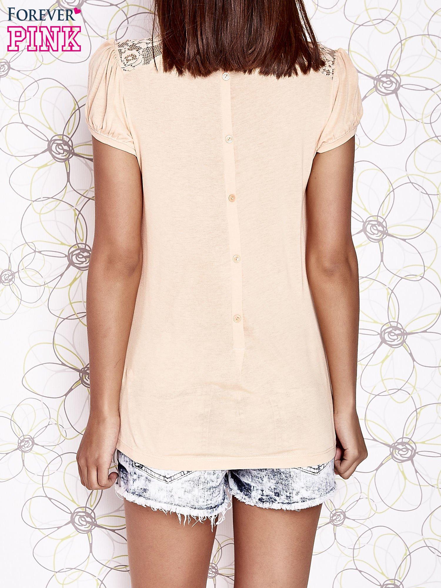 Jasnopomarańczowy t-shirt z ażurowym motywem