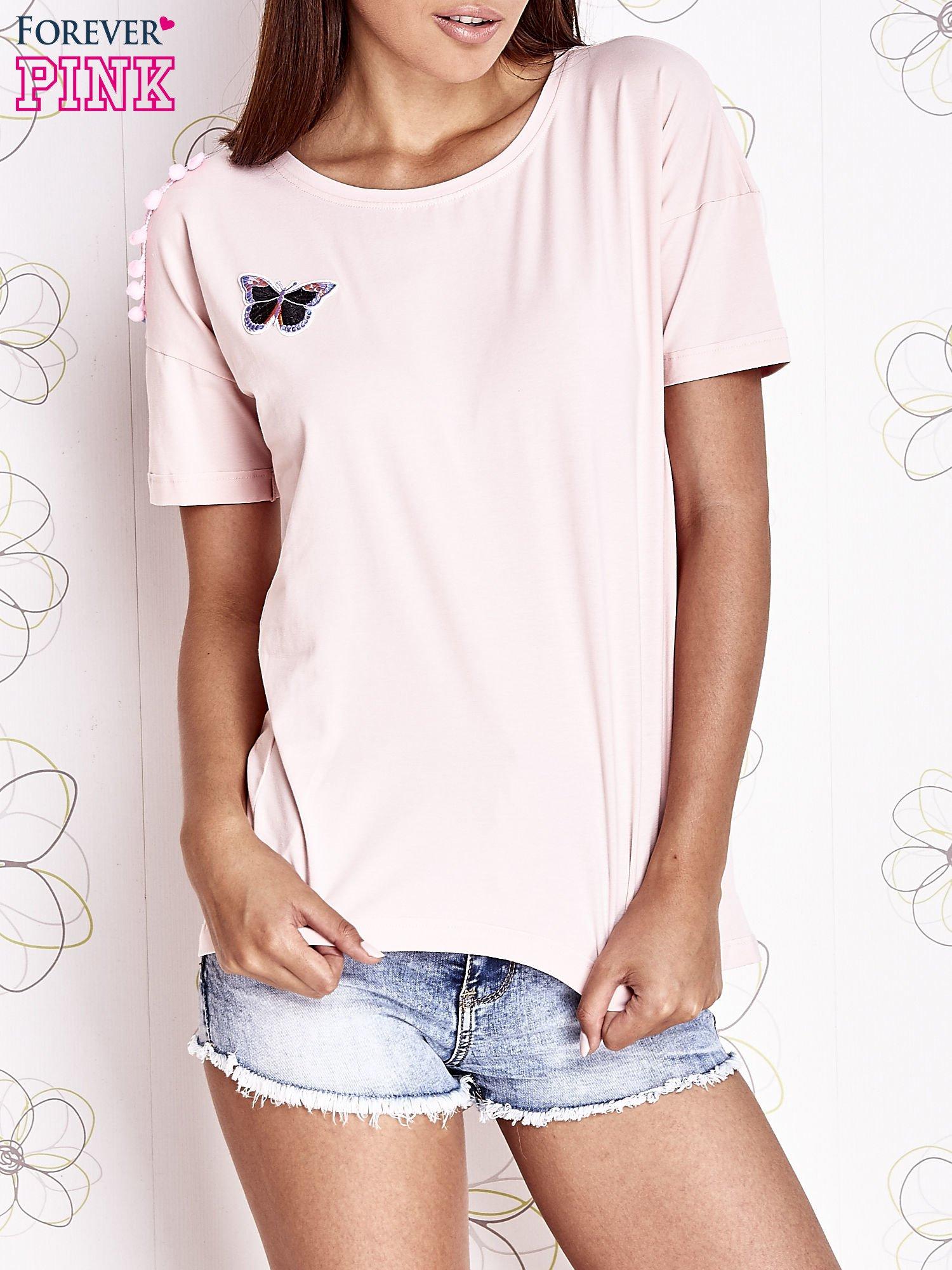 Jasnoróżowy t-shirt z naszywką motyla i pomponikami                                  zdj.                                  1