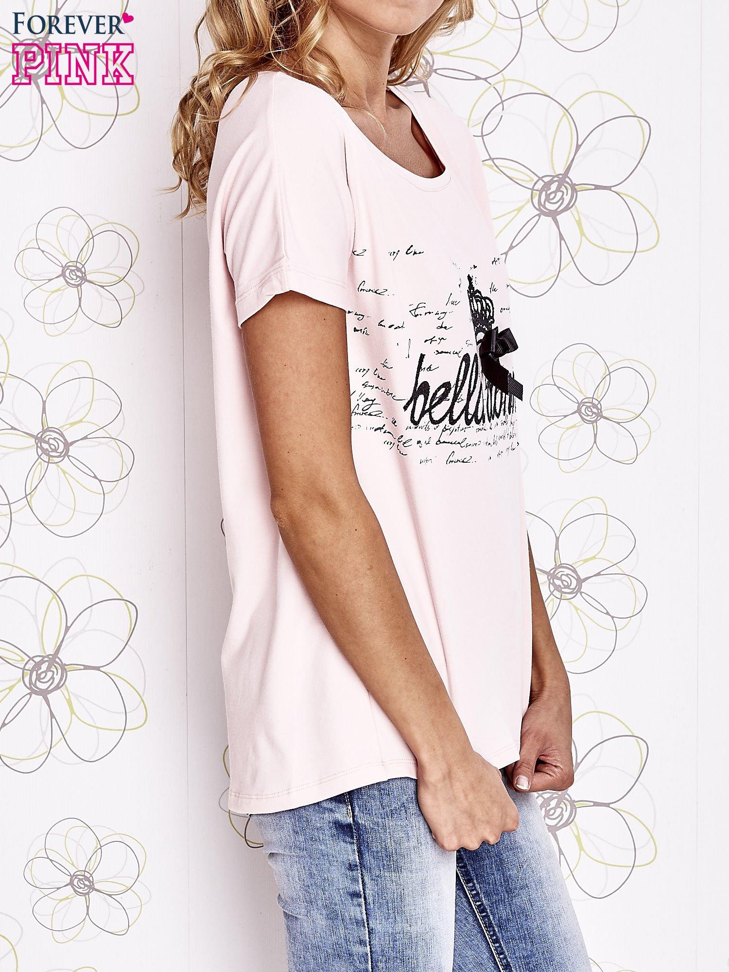 Jasnoróżowy t-shirt z ozdobnym napisem i kokardą                                  zdj.                                  3