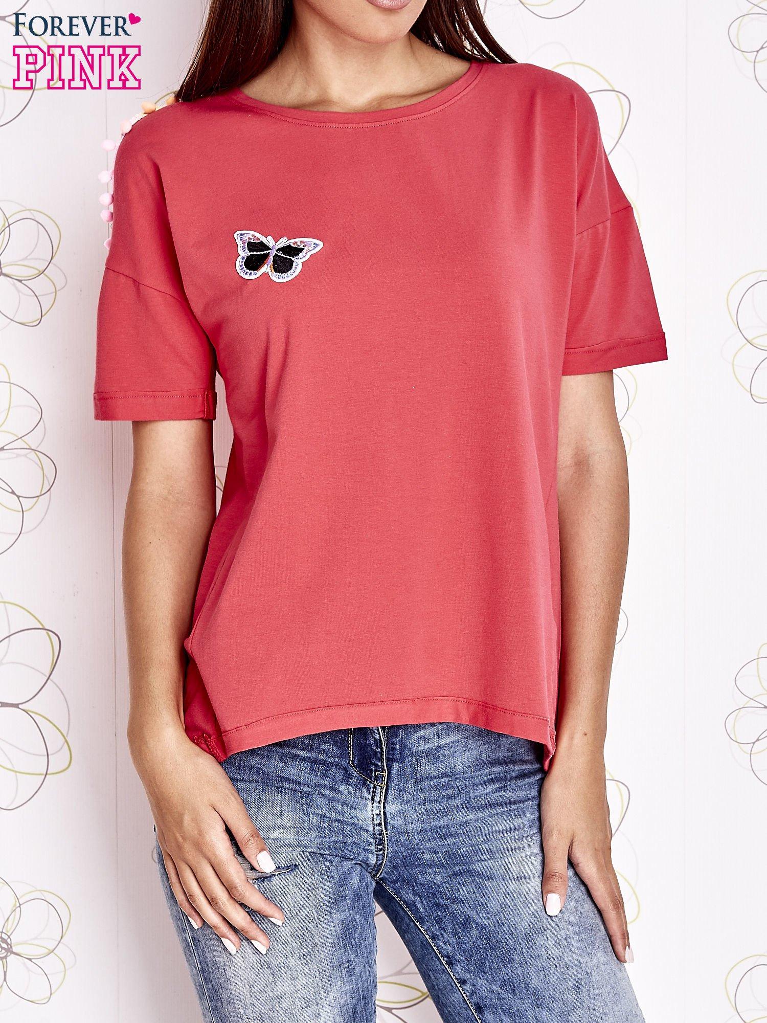 Koralowy t-shirt z naszywką motyla i pomponikami                                  zdj.                                  1
