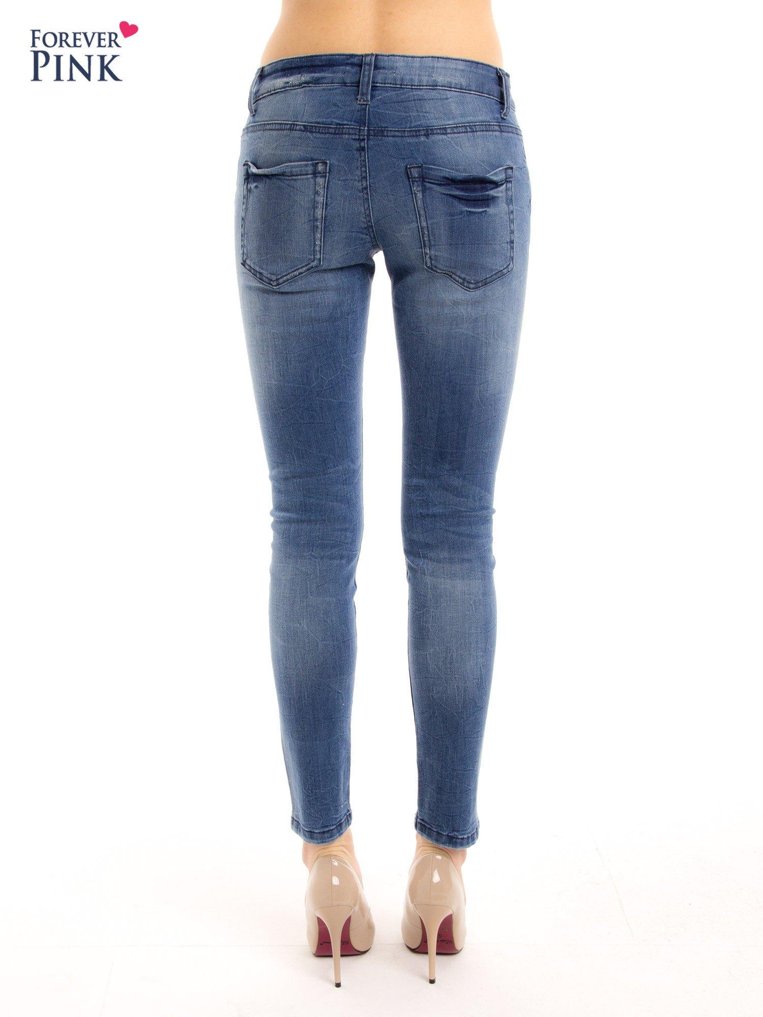 Niebieskie jeansy rurki z przetarciami                                  zdj.                                  3