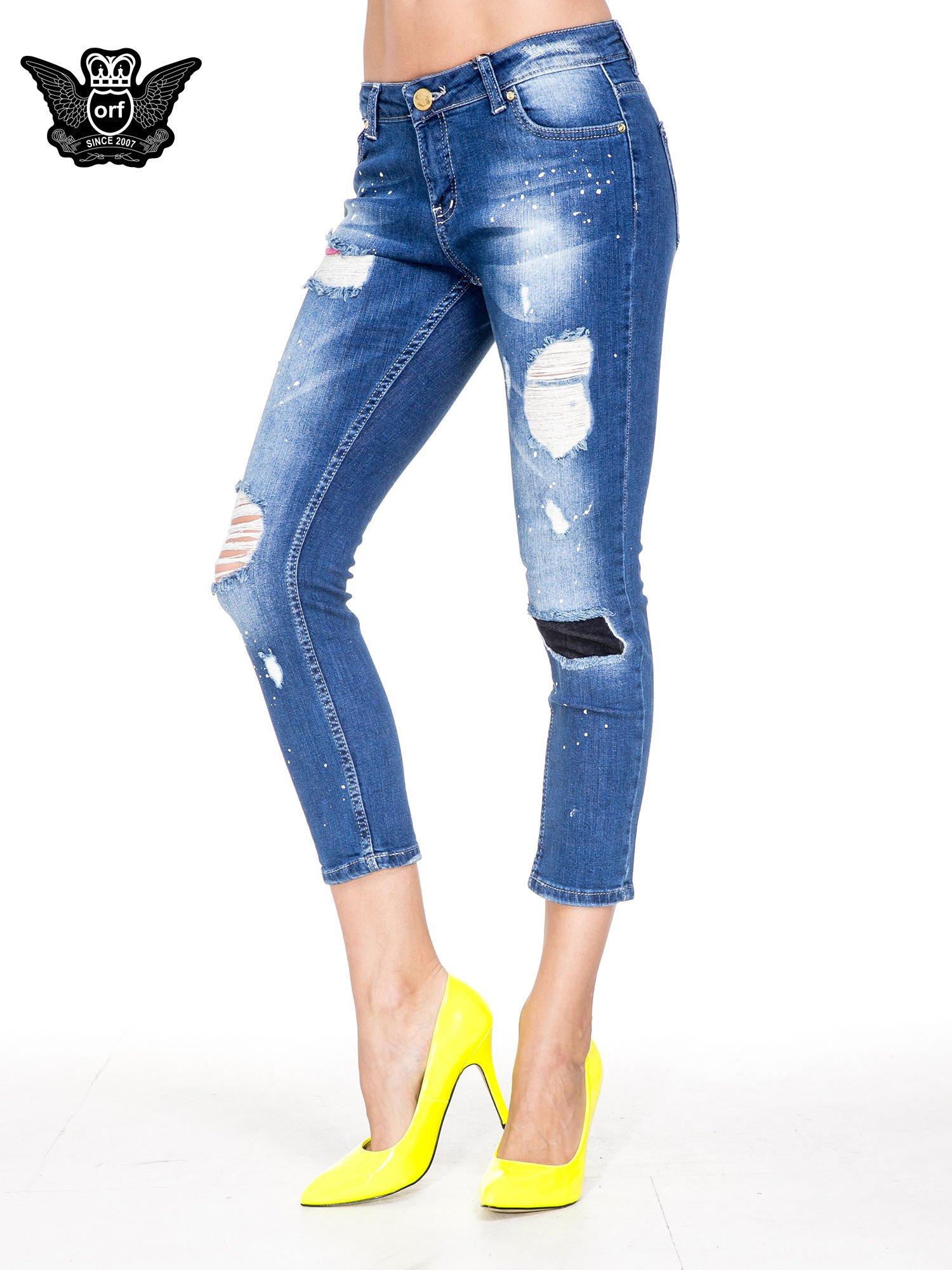 Niebieskie spodnie jeansowe długości 7/8 z łatami i przetarciami                                  zdj.                                  1