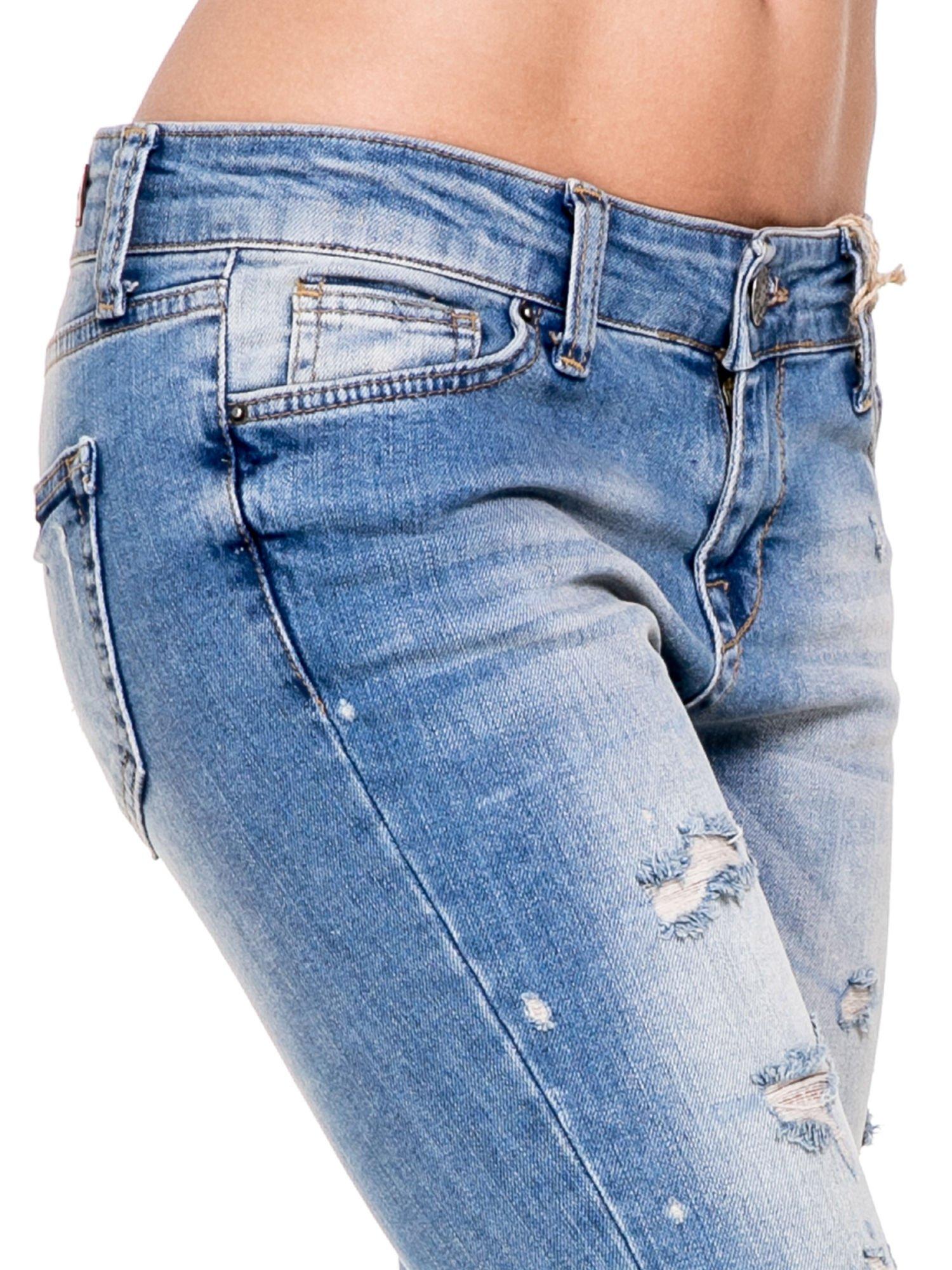 Niebieskie spodnie jeansowe do połowy łydki z licznymi przetarciami                                  zdj.                                  7