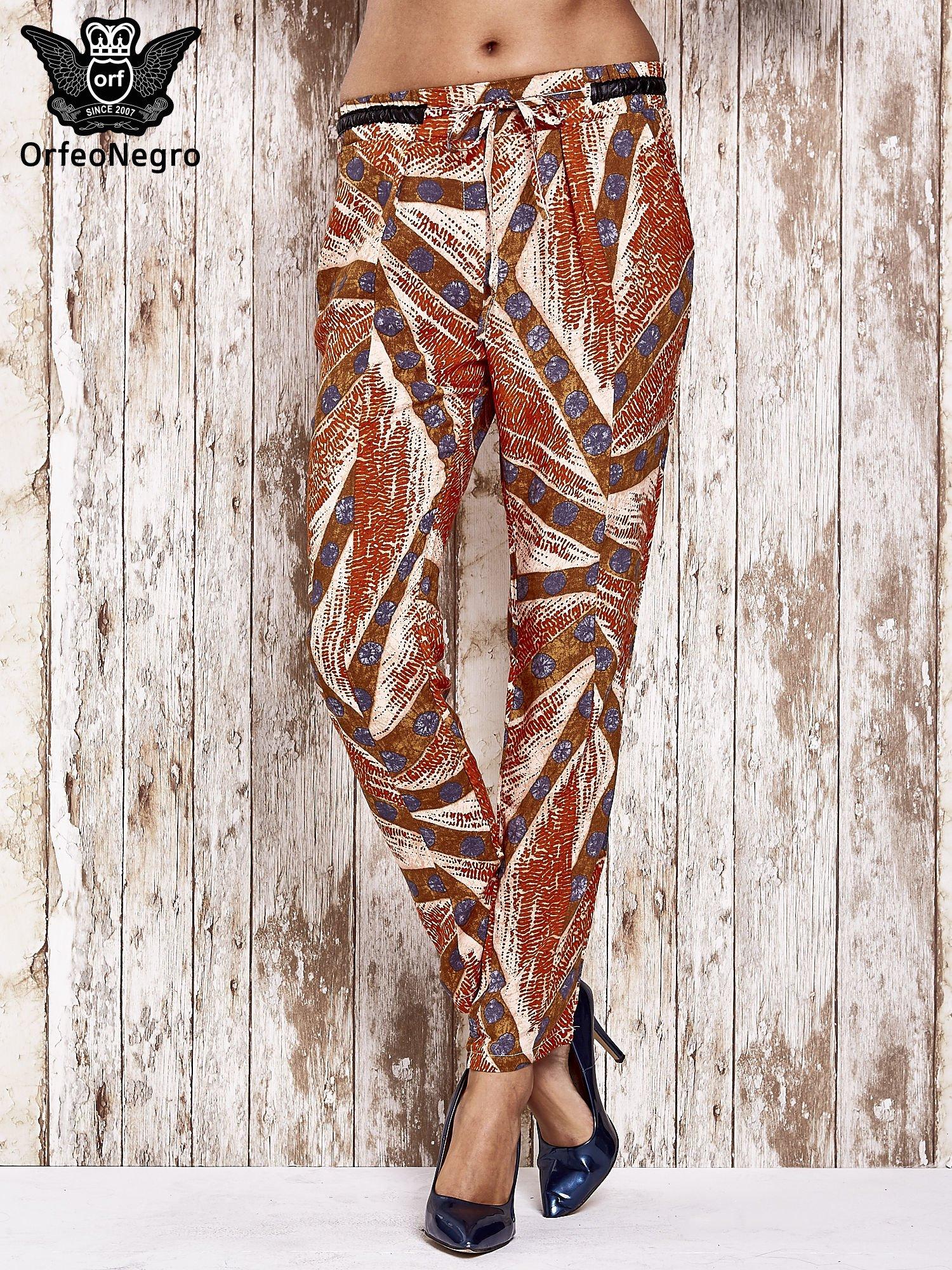 Pomarańczowe lejące spodnie z artystycznym nadrukiem                                  zdj.                                  1