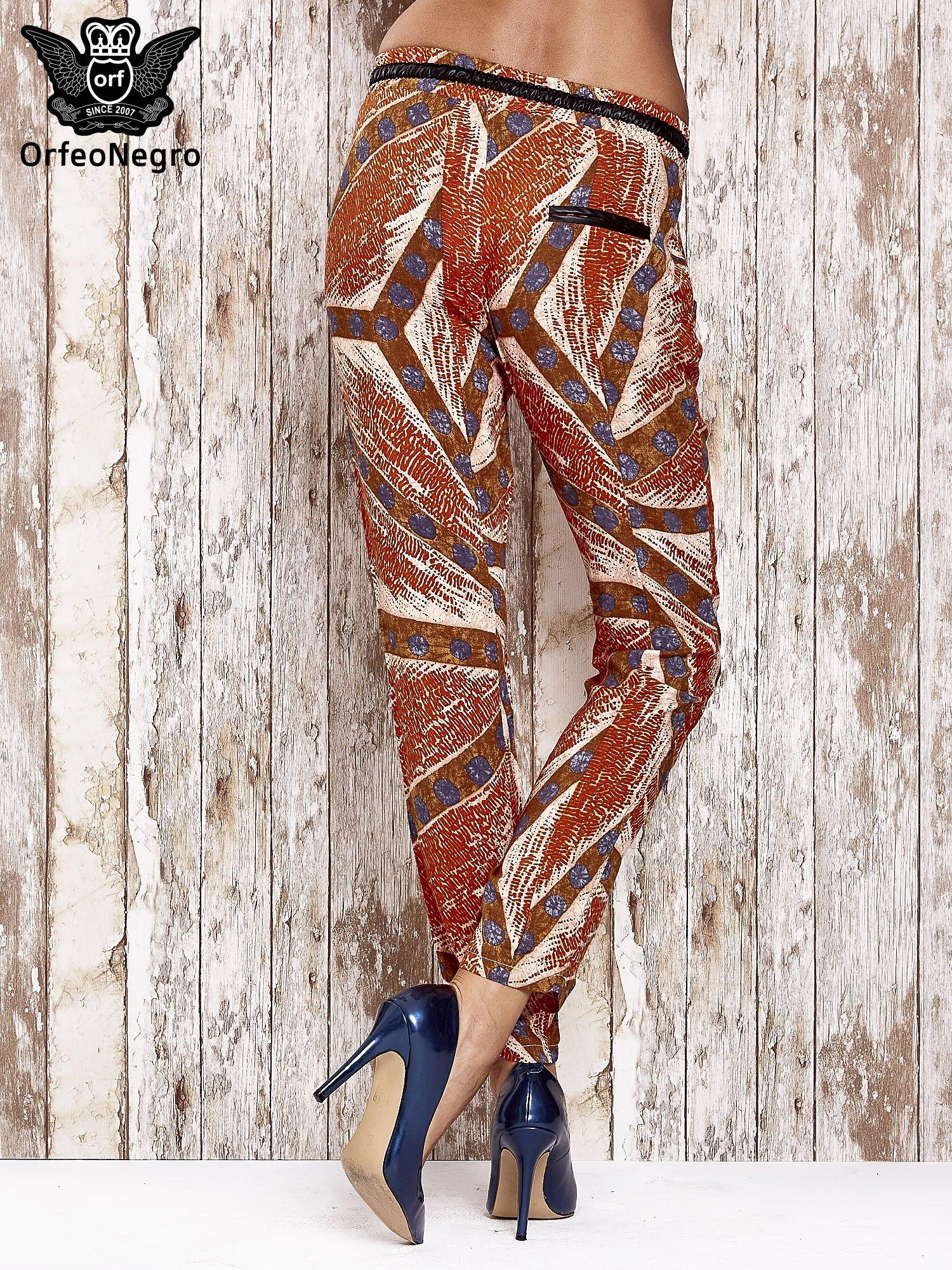 Pomarańczowe lejące spodnie z artystycznym nadrukiem                                  zdj.                                  2