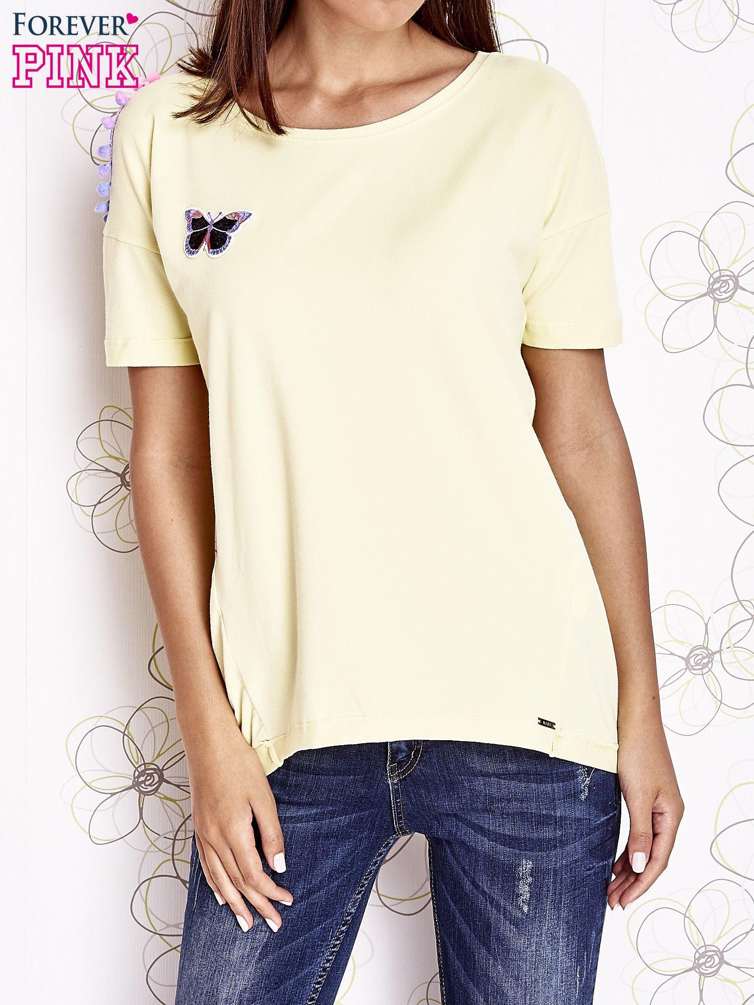 Żółty t-shirt z naszywką motyla i pomponami                                  zdj.                                  1