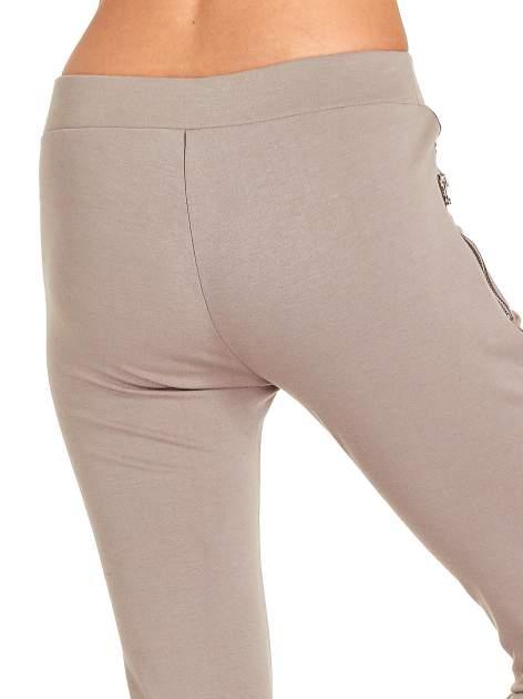 Beżowe spodnie materiałowe tregginsy ze skórzanym lampasem i zamkami                                  zdj.                                  7