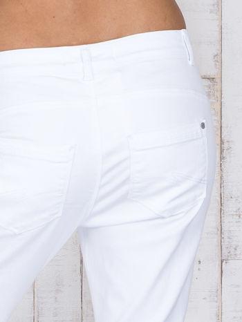 Białe jeansowe spodnie z przetarciami i guzikami                                  zdj.                                  5
