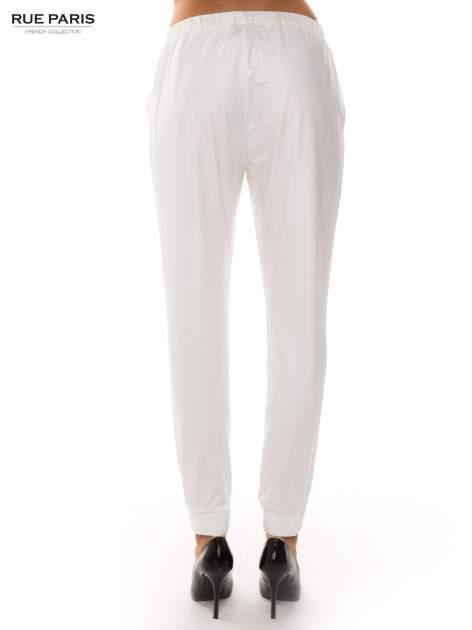 Białe spodnie dresowe ze zwężanymi nogawkami z efektem połysku                                  zdj.                                  4