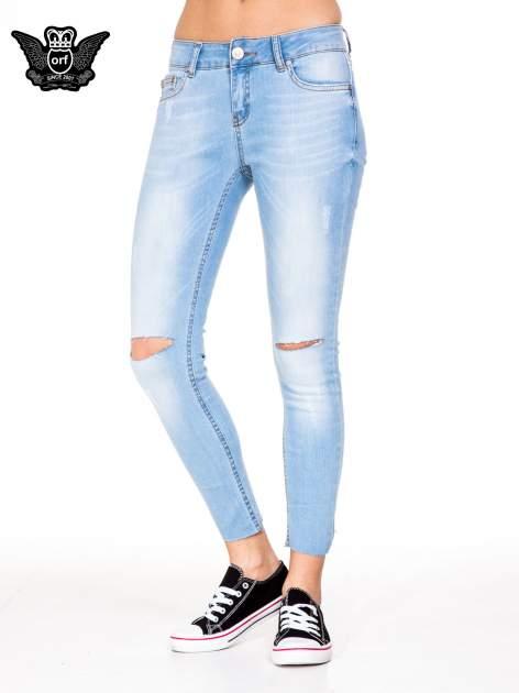 Błękitne spodnie jeansowe rurki z rozdarciam na kolanach