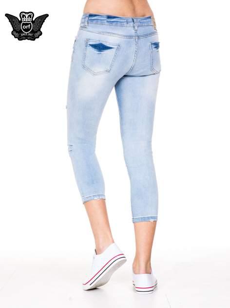 Błękitne spodnie skinny jeans do połowy łydki z rozdarciami                                  zdj.                                  4