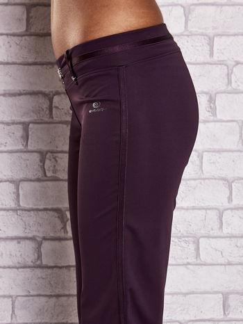 Ciemnofioletowe spodnie dresowe z ozdobnym paskiem                                  zdj.                                  5