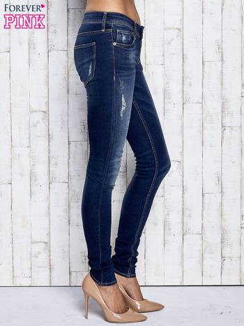 Ciemnoniebieskie spodnie jeansowe z przetarciami                              zdj.                              2