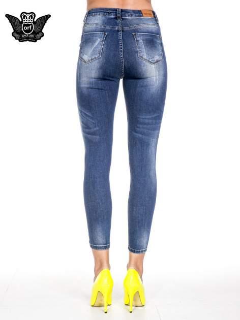 Ciemnoniebieskie spodnie skinny jeans z przecieraną nogawką z przodu                                  zdj.                                  5