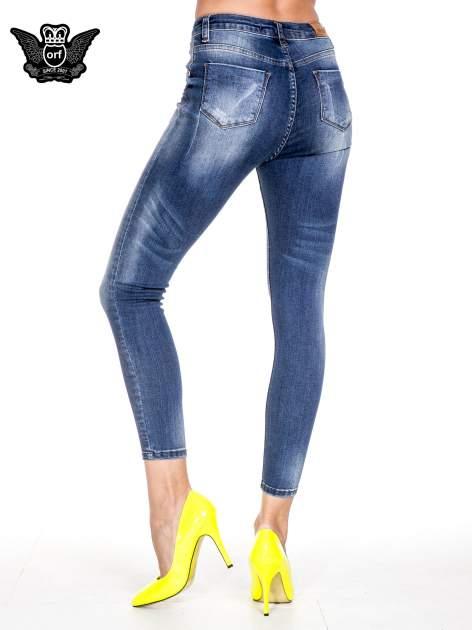 Ciemnoniebieskie spodnie skinny jeans z przecieraną nogawką z przodu                                  zdj.                                  4