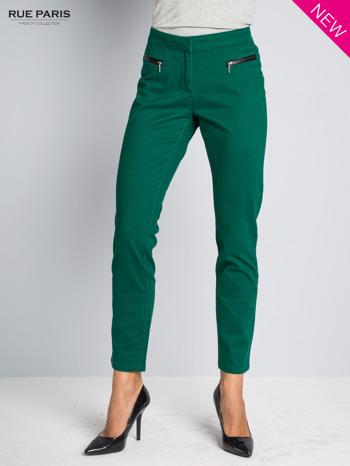 Ciemnozielone spodnie cygaretki ze skórzaną lamówką przy kieszeniach