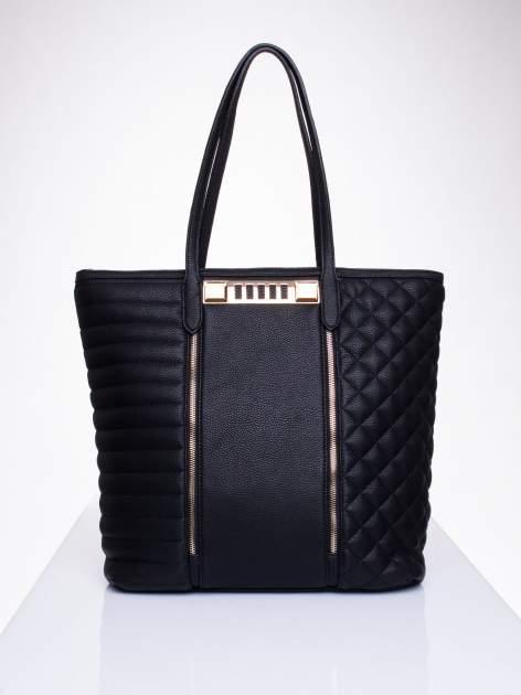 Czarna torba ze złoceniami i asymetrycznym pikowaniem po bokach