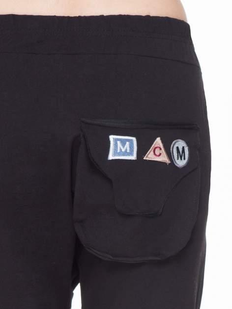 Czarne dresowe spodnie baggy z guzikami i ozdobnymi kieszonkami                                  zdj.                                  6