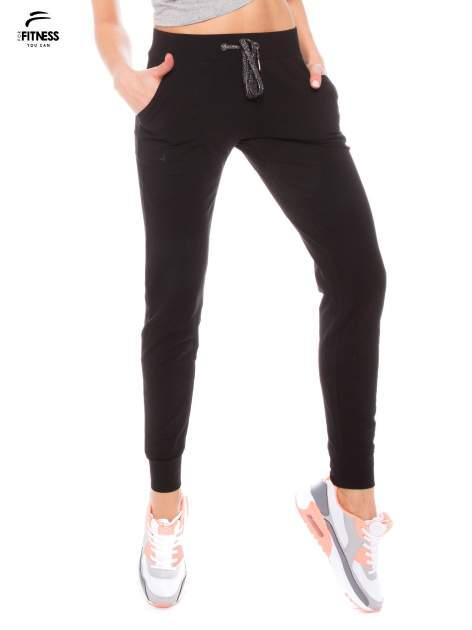 Czarne dresowe spodnie damskie ze ściągaczem i błyszczącym sznurkiem