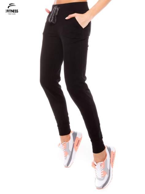 Czarne dresowe spodnie damskie ze ściągaczem i błyszczącym sznurkiem                                  zdj.                                  2