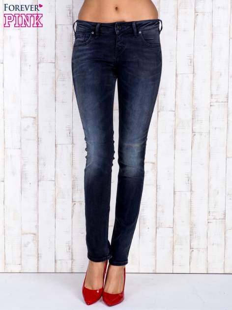 Czarne jeansowe spodnie rurki z kieszeniami i przetarciami