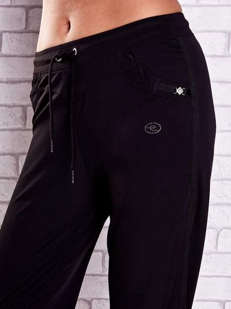Czarne spodnie capri z dżetami i lampasami                              zdj.                              4