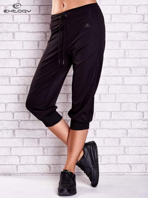 Czarne spodnie capri z lampasami i troczkami PLUS SIZE                                  zdj.                                  1