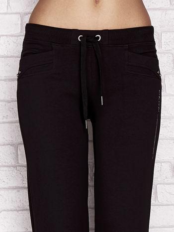 Czarne spodnie dresowe capri z aplikacją na kieszeniach                                  zdj.                                  4